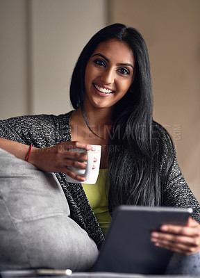 Buy stock photo Portrait of an attractive young woman surfing the net while sitting on her sofa at home