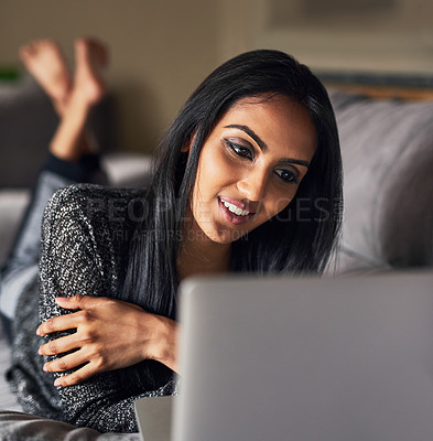 Buy stock photo Shot of an attractive young woman surfing the net while lying on her sofa at home