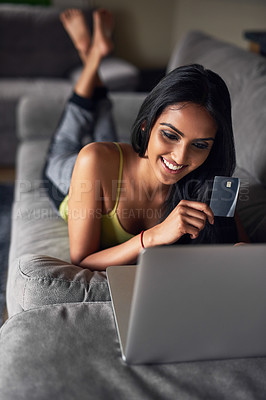 Buy stock photo Shot of an attractive young woman shopping online while lying on her sofa at home