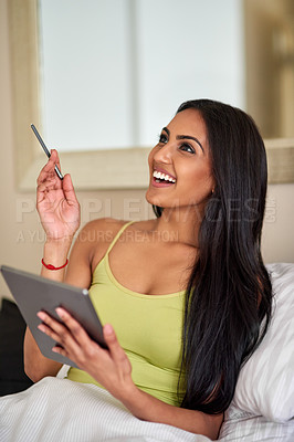 Buy stock photo Shot of a thoughtful young woman using a digital tablet in bed