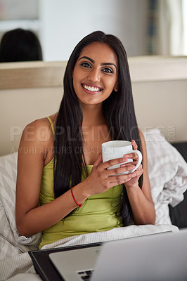 Buy stock photo Shot of a relaxed young woman using a laptop and drinking coffee in bed