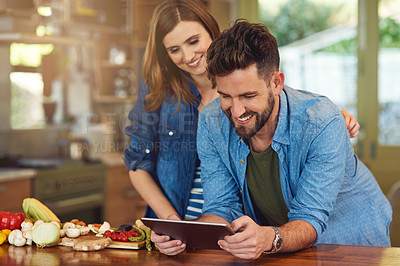 Buy stock photo Shot of a happy young couple using a digital tablet while preparing a healthy meal together at home