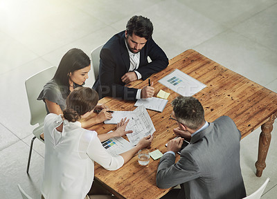 Buy stock photo Shot of a group of colleagues sitting around a meeting tablet in the office