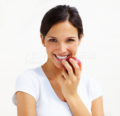 Buy stock photo Portrait of pretty young lady eating a fresh apple against bright background
