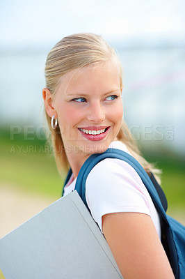 Buy stock photo Happy young female student carrying her bag and a folder while outdoors