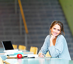 Young charming woman smiling while making notes