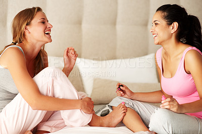 Buy stock photo Portrait of happy young women applying nail paint while sitting on the bed