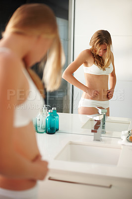 Buy stock photo Portrait of sexy young woman checking fats on her belly in the bathroom mirror