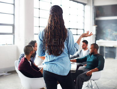 Buy stock photo Rearview shot of a woman giving a presentation to colleagues in an office