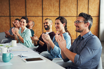Buy stock photo Shot of a group of colleagues clapping together at a table in an office