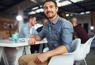 Buy stock photo Portrait of a mature man sitting at a table in an office with colleagues working in the background