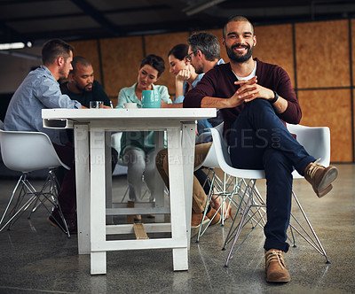 Buy stock photo Portrait of a young man sitting at a table in an office with colleagues working in the background