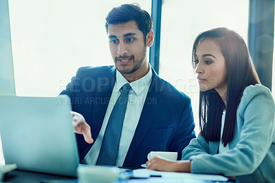 Buy stock photo Shot of a two businesspeople talking together over a laptop while working in an office