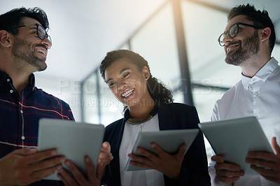 Buy stock photo Shot of three colleagues using digital tablets while standing together in an office