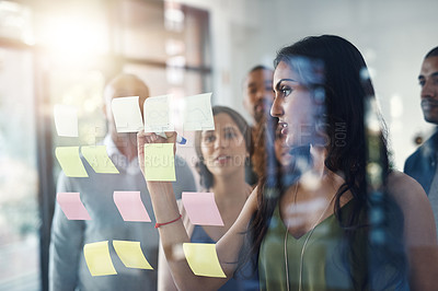 Buy stock photo Shot of a group of coworkers brainstorming on a glass wall