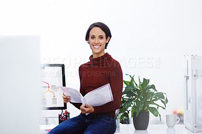 Buy stock photo Portrait of a confident young businesswoman reading some paperwork in her office