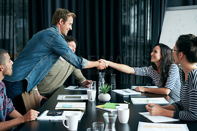 Buy stock photo Shot of two colleagues shaking hands in a boardroom while coworkers look on