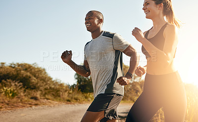 Buy stock photo Shot of a fit young couple going for a run outdoors