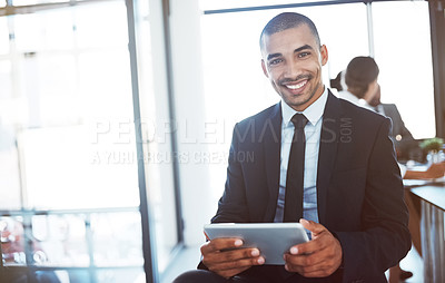 Buy stock photo Portrait of a young businessman using a digital tablet during a meeting at work