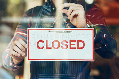 Buy stock photo Closeup shot of a young man hanging up a closed sign in a shop window