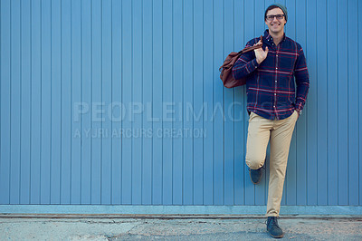 Buy stock photo Portrait of a handsome young man leaning against a blue wall
