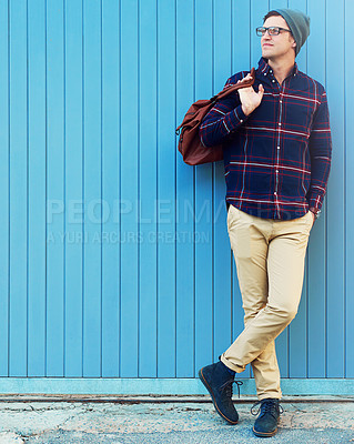 Buy stock photo Shot of a handsome young man leaning against a blue wall