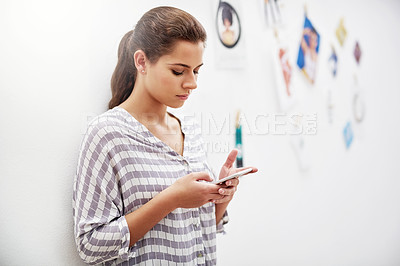 Buy stock photo Shot of an attractive young designer sending a text while standing in her studio