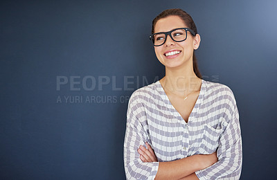Buy stock photo Studio shot of an attractive and happy young woman posing against a dark background