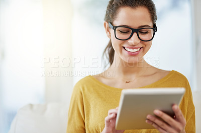 Buy stock photo Shot of an attractive young woman using her tablet while relaxing on the sofa at home