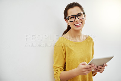 Buy stock photo Portrait of an attractive young woman using her tablet against a grey background