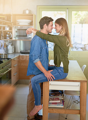 Buy stock photo Shot of an affectionate young couple hugging in their kitchen