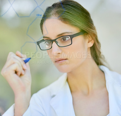 Buy stock photo Shot of a scientist writing formulas on a glass wall