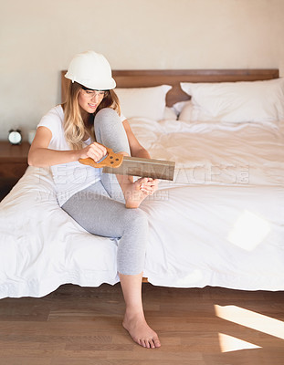 Buy stock photo Shot of a young woman trying to cut her toenails with a saw at home