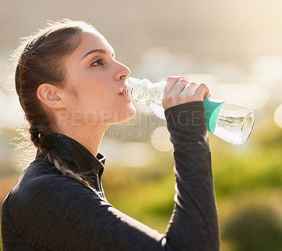 Buy stock photo Shot of an attractive young woman drinking water during her workout