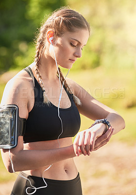 Buy stock photo Shot of an attractive young woman listening to music while timing her run