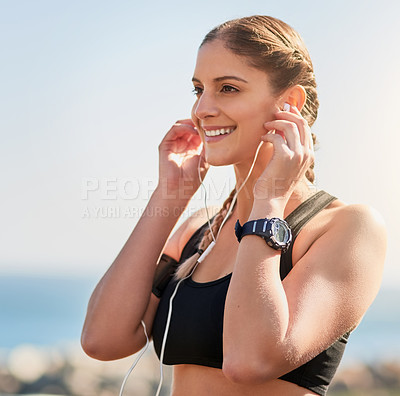 Buy stock photo Shot of an attractive young woman putting earphones in her ears in preparation for a run