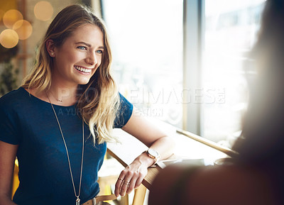 Buy stock photo Cropped shot of a woman chatting to her friend in a cafe