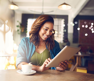 Buy stock photo Cropped shot of an attractive young woman using a digital tablet in a cafe