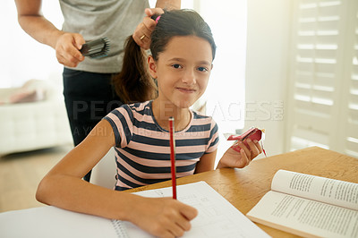 Buy stock photo Shot of a young girl doing her homework while her father brush her hair