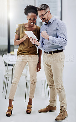 Buy stock photo Shot of a businessman showing something to his colleague on his tablet in the office