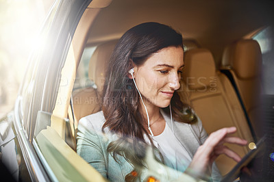 Buy stock photo Shot of a beautiful businesswoman using her tablet while traveling in the back seat of a car