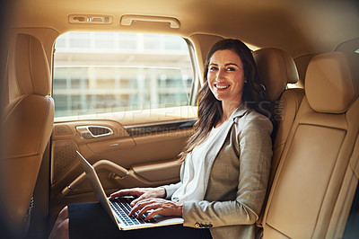 Buy stock photo Portrait of a beautiful businesswoman working on her laptop while traveling in the back seat of a car