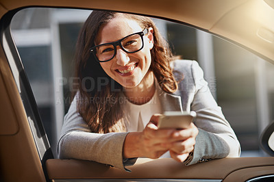 Buy stock photo Shot of a happy businesswoman leaning into the window of a car while texting on her cellphone
