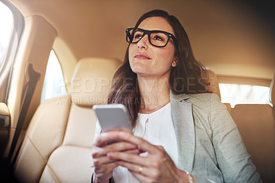 Buy stock photo Shot of a beautiful businesswoman texting on her phone while traveling in the back seat of a car