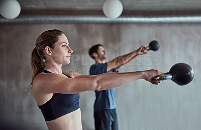 Buy stock photo Shot of two young athletes working out using kettle bells