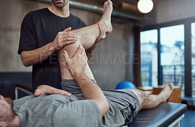 Buy stock photo Shot of a young man visiting his physiotherapist for a rehabilitation session