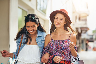 Buy stock photo Shot of two young friends enjoying a day of shopping