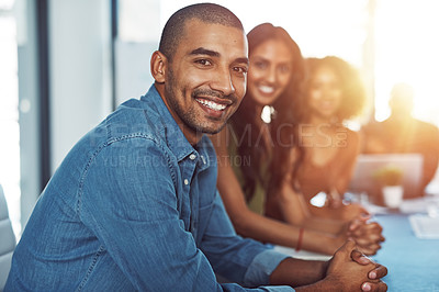 Buy stock photo Portrait of a businessman sitting in a boardroom with his colleagues blurred out in the background