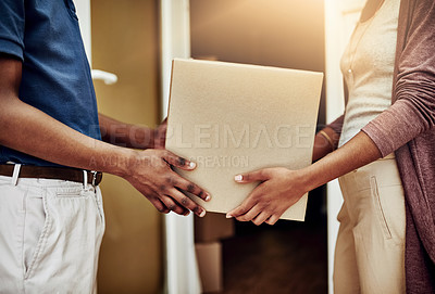 Buy stock photo Shot of a postal worker delivering a package to an unrecognizable female customer
