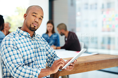 Buy stock photo Portrait of a handsome young man using his tablet while sitting in the boardroom during a meeting